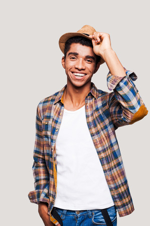 Open and sociable.  Handsome young Afro-American hipster holding hand on his hat while standing against grey background Stock Photo - 32619608