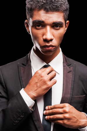 Looking sharp. Fashionable young Afro-American man adjusting his necktie while standing against black background photo
