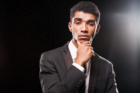 A keen eye for style.  Fashionable young Afro-American man holding hand on chin while standing against black background photo