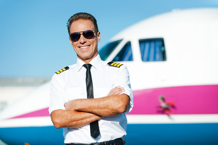 uniform attire: Confident pilot. Confident male pilot in uniform keeping arms crossed and smiling with airplane in the background Stock Photo