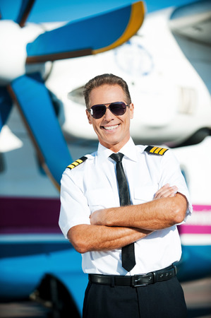 My job is my passion. Confident male pilot in uniform keeping arms crossed and smiling while standing in front of the airplane photo