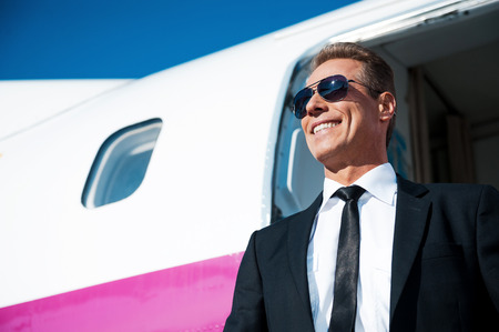 i am here: Here I am! Low angle view of confident mature businessman getting out of airplane and smiling Stock Photo
