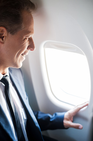 corporate airplane: What a great view! Happy mature businessman sitting at his seat in airplane and looking through airplane window