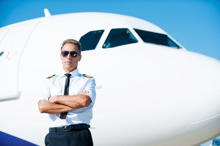 Ready for the skies. Confident male pilot in uniform keeping arms crossed while standing near airplane