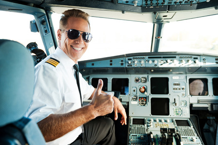 airplane: Ready to flight. Rear view of confident male pilot showing his thumb up and smiling while sitting in cockpit Stock Photo