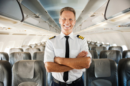 private airplane: This is my plane. Confident male pilot in uniform keeping arms crossed and smiling while standing inside of the airplane