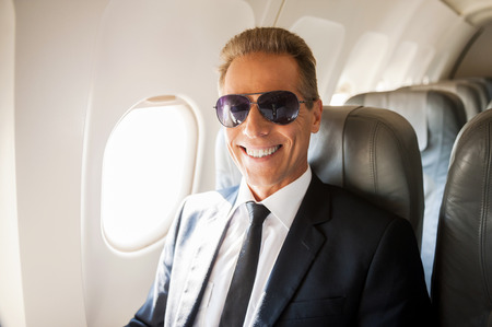 passenger aircraft: Businessman in airplane. Confident mature businessman sitting at his seat in airplane and smiling