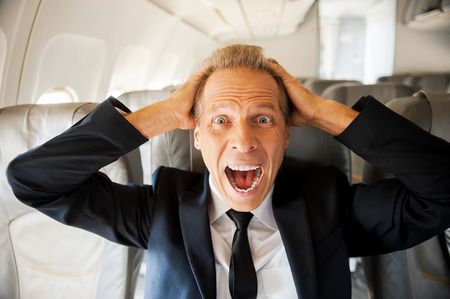 airplane: Fear of flight. Shocked mature businessman touching his head with hands and looking at camera while sitting at his seat in airplane