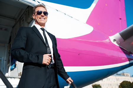 just arrived: Just arrived. Low angle view of confident mature businessman getting out of airplane and smiling
