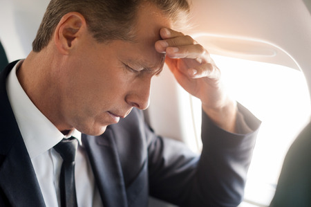 private airplane: Feeling headache. Frustrated mature businessman touching his forehead with hand and keeping eyes closed while sitting at his seat in airplane