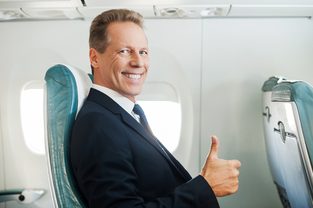 Ready to flight. Confident mature businessman sitting at his seat in airplane and smiling