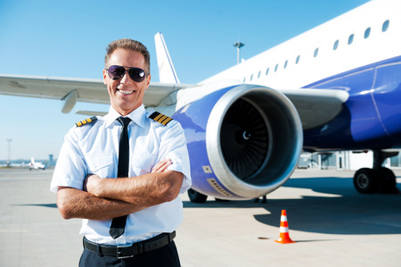 pilot wings: Confident pilot. Confident male pilot in uniform keeping arms crossed and smiling with airplane in the background Stock Photo