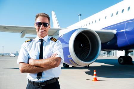Zelfverzekerd piloot. Zekere mannelijke piloot in uniform houden van de armen gekruist en lachend met vliegtuig op de achtergrond Stockfoto