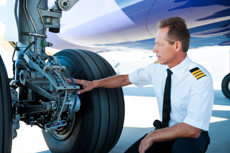 uniform attire: Checking the wheels. Confident male pilot in uniform examining an airplane wheels