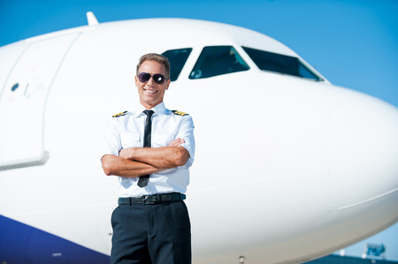 uniform attire: Sky is my passion. Confident male pilot in uniform keeping arms crossed and smiling with airplane in the background