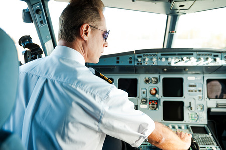 piloto de avion: Listo para despegar. Vista trasera del piloto masculino conf�a sentado en la cabina y conseguir un avi�n listo para el vuelo