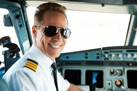조종석에 파일럿. 자신감이 남성 파일럿의 후면보기 조종석에 앉아있는 동안 어깨 너머로보고 웃 고