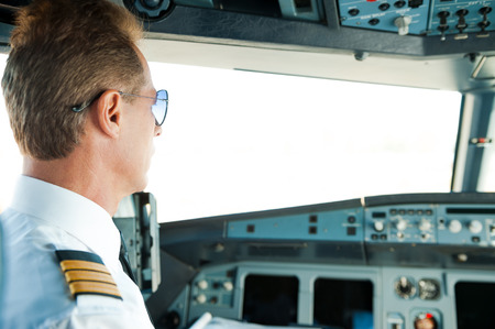 corporate airplane: Getting ready to flight. Rear view of confident male pilot sitting in airplane cockpit
