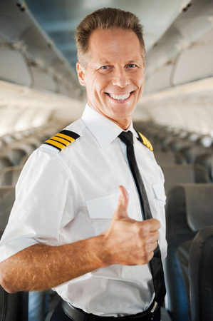 I love my job! Confident male pilot in uniform showing his thumb up and smiling while standing inside of the airplane photo