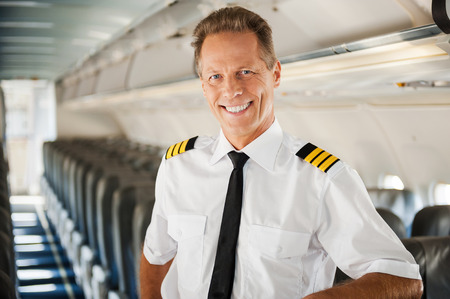 uniform attire: Feeling confident in his plane. Confident male pilot in uniform leaning at the passenger seat and smiling while standing inside of the airplane Stock Photo