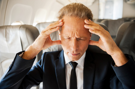 Hard flight. Frustrated mature businessman touching his head with hands and keeping eyes closed while sitting at his seat in airplane photo
