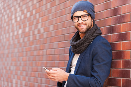 text: Typing text message. Side view of handsome young man in smart casual wear holding mobile phone while leaning at the brick wall