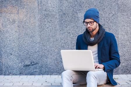 그물을 야외에서 서핑. 야외에서 앉아있는 동안 노트북에서 작동하는 스마트 캐주얼 착용 잘 생긴 젊은 남자