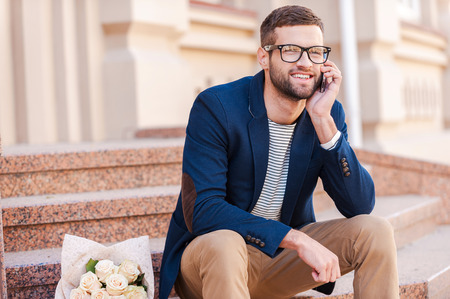 nude young: Waiting for you! Handsome young man in smart jacket talking on the mobile phone and smiling while sitting on the staircase with bouquet of roses laying near him