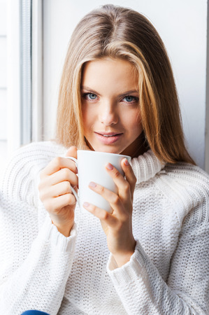 warmness: Charming warmness. Beautiful young woman sitting near the window at her apartment holding a cup of coffee
