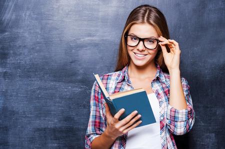 그녀의 지식에 자신감이 있습니다. 책을 들고 칠판에 대하여 서있는 동안 웃는 쾌활한 젊은 여성