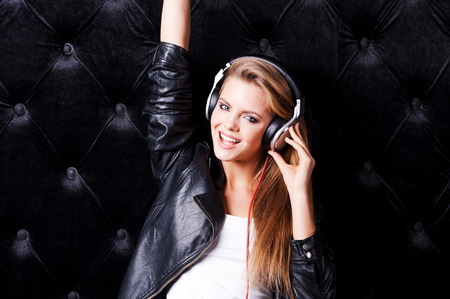 musically: Musically taking fun. Beautiful young woman with make up and in headphones posing against black  Stock Photo
