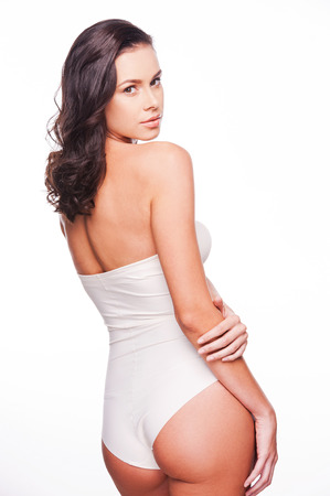 nude female buttocks: Proud of her perfect body. Rear view of attractive young woman in lingerie posing against white