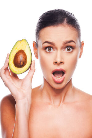 Avocado Surprised young shirtless woman holding avocado in her hand and keeping mouth open while standing against white  photo