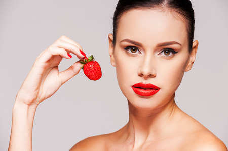 Sweet temptation. Beautiful young shirtless woman holding strawberry in her hand while standing against grey background photo