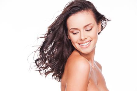 modelos desnudas: Ajuste a m� mismo libre. Hermosa joven mirando sobre su hombro y sonriendo mientras est� de pie en contra de blancos Foto de archivo