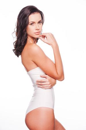shape: Beauté confiant. Vue de côté de jeune femme séduisante de cheveux noirs posant sur blanc Banque d'images