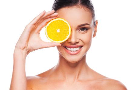健康的なライフ スタイルのための素晴らしい料理。白に対して立っている間彼女の目の前にオレンジ色の部分を保持している美しい若い上半身裸の