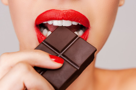 indulging: Indulging in a sweet affair with chocolate. Close-up of a beautiful women holding finger on her red lips while standing against grey