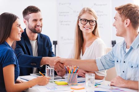 dandose la mano: Bienvenido a bordo! Grupo de gente de negocios alegre sentado en la mesa juntos, mientras que dos hombres d�ndose la mano y sonriendo