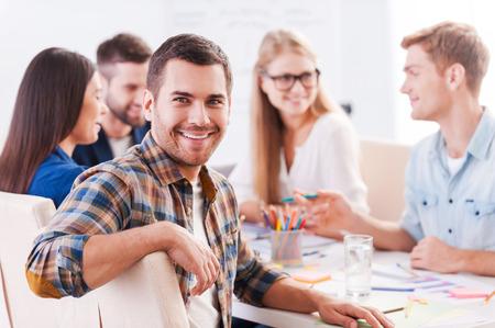 Gelukkig om een deel van de creatieve team. Groep van vrolijke mensen uit het bedrijfsleven in smart casual wear zitten samen aan de tafel en bespreken van iets terwijl knappe man kijken naar de camera en lacht