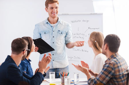 Great presentation! Group of business people in smart casual wear sitting together at the table and applauding to their colleague standing near whiteboard and smiling