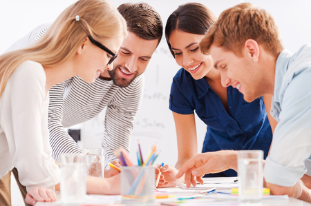 smart man: Creative team at work. Four cheerful business people in smart casual wear discussing something while leaning at the table Stock Photo