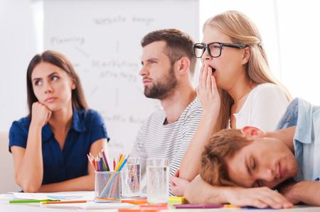 dormir: Presentaci�n aburrida. Grupo de j�venes empresarios en la ropa de sport elegante que parece aburrida mientras estaba sentado junto a la mesa y mirando a otro lado Foto de archivo