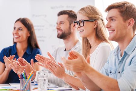Groep van gelukkige mensen uit het bedrijfsleven in smart casual wear zitten samen aan tafel en applaudisseren aan iemand Stockfoto
