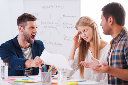 This is all wrong! Two frustrated business people sitting at the table and gesturing while their furious boss holding paper and shouting Foto de archivo