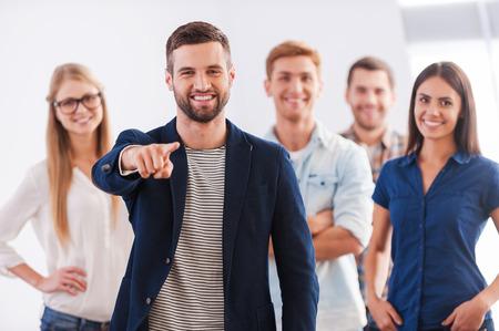 Word lid van ons team! Mooie jonge vrouw toont haar duim omhoog en glimlachen terwijl groep van gelukkige jonge mensen staan Stockfoto