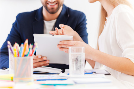 great idea: It is a great idea! Close-up of two confident business people in smart casual wear sitting at the table together and discussing something while looking at the digital tablet