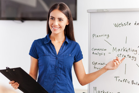 Talking about strategy. Confident young woman in smart casual wear standing near whiteboard and pointing it with smile