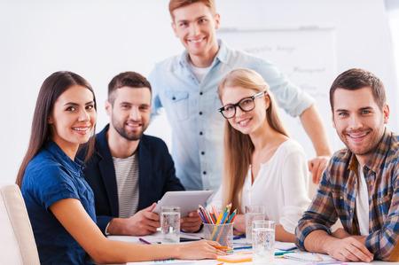personas sentadas: Listo para una lluvia de ideas. Grupo de gente de negocios feliz en la ropa de sport elegante que se sienta junto a la mesa y mirando a la c�mara