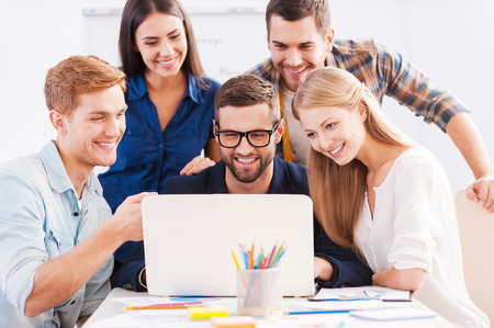 영감. 스마트 캐주얼 쾌활한 비즈니스 사람들이 함께 노트북을보고 웃 고의 그룹